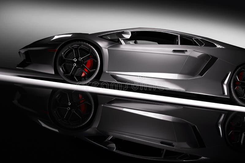 在聚光灯,黑背景的灰色快速的跑车 发光,新,豪华 皇族释放例证