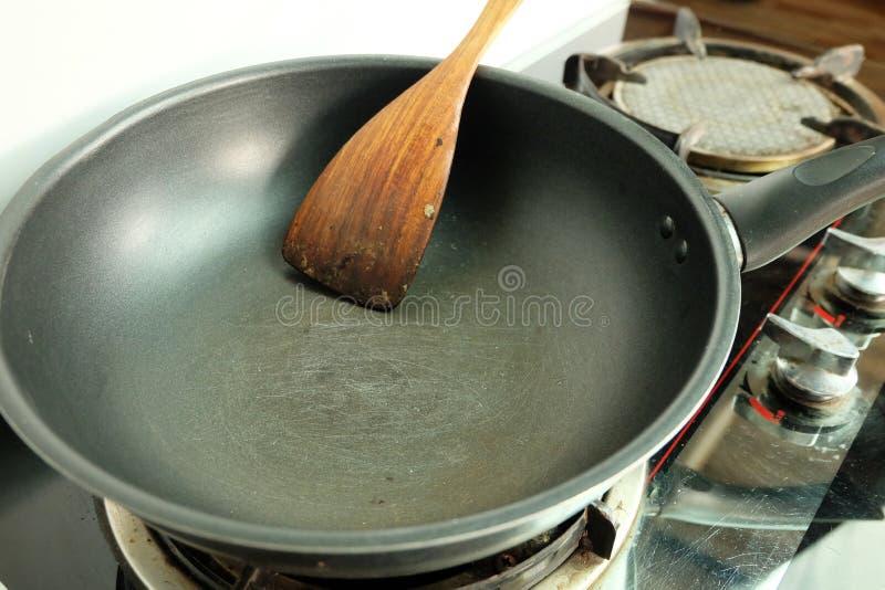 在聚四氟乙烯煎锅的抓痕有在煤气炉的小铲的 图库摄影