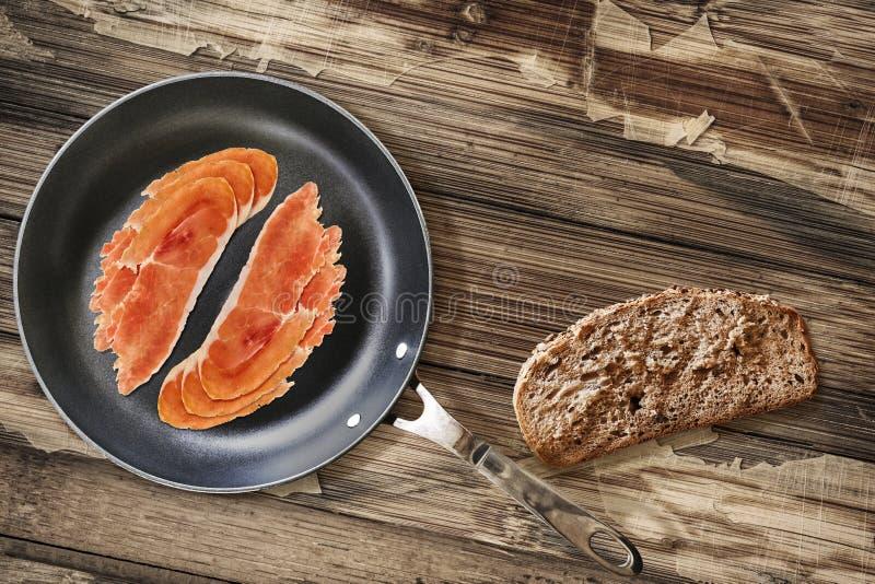 在聚四氟乙烯煎锅的熏火腿更卤莽有非常面包切片的 库存图片