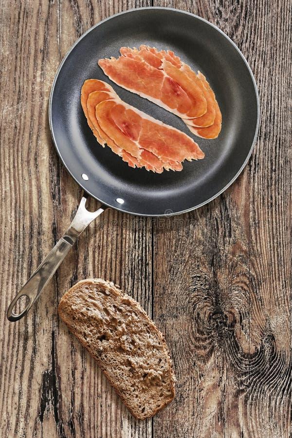 在聚四氟乙烯煎锅的熏火腿更卤莽有非常面包切片的 免版税库存照片