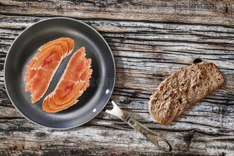 在聚四氟乙烯煎锅的熏火腿更卤莽有非常面包切片的 图库摄影