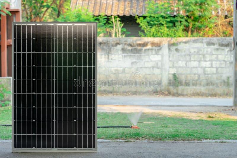 在聪明的家庭电力量的太阳能电池控制自动水喷水隆头在绿草围场 免版税库存照片