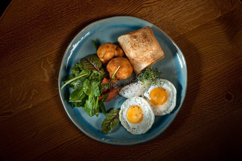在肉的炒蛋用油煎的土豆和多士 免版税库存照片