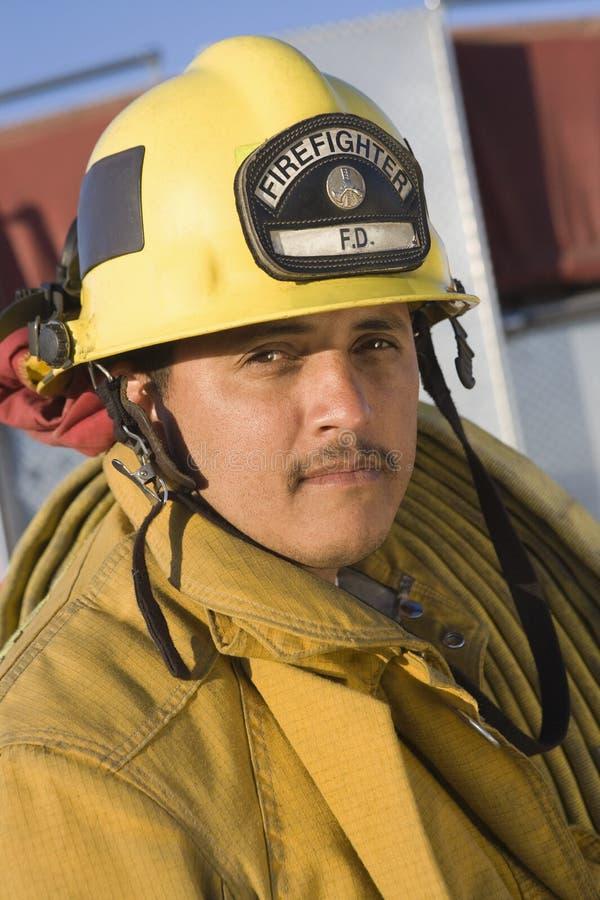 在肩膀的成熟消防队员运载的灭火水龙带 库存照片