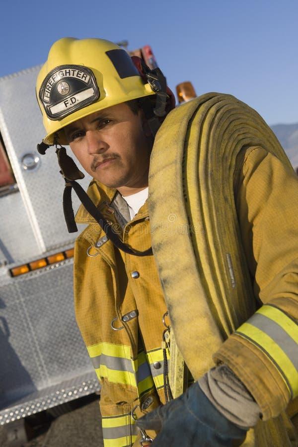 在肩膀的消防队员运载的灭火水龙带 免版税库存照片