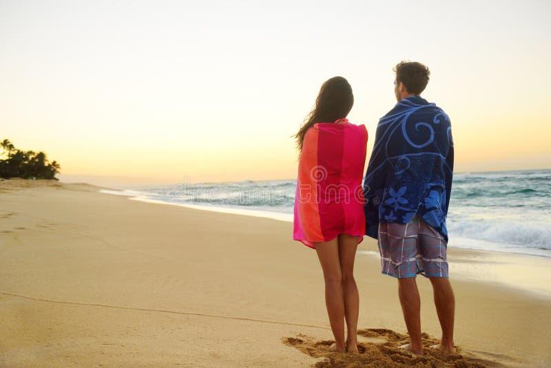 在肩膀的年轻夫妇毛巾在海滩沙子 库存照片