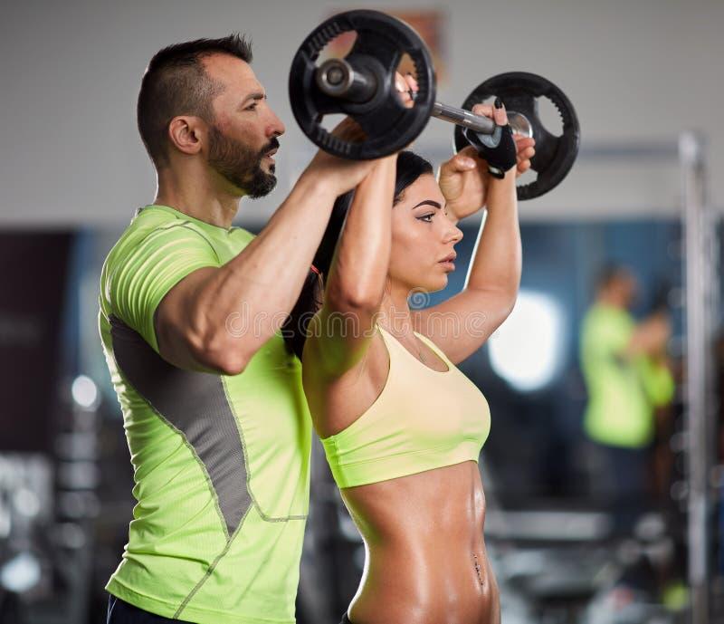 在肩膀锻炼的个人教练员 免版税库存照片