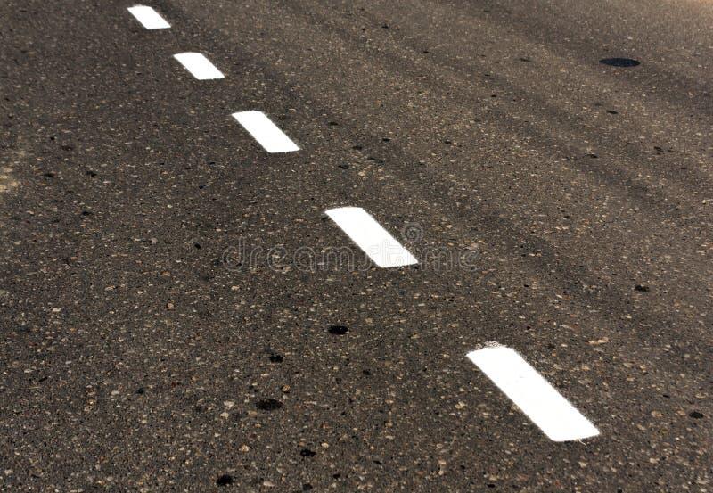 在肮脏的沥青纹理的白色路线 免版税库存照片