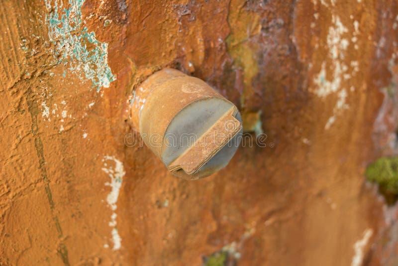 在肮脏的混凝土墙-绿色庭院上的特写镜头发霉的老PVC盖帽 免版税库存照片