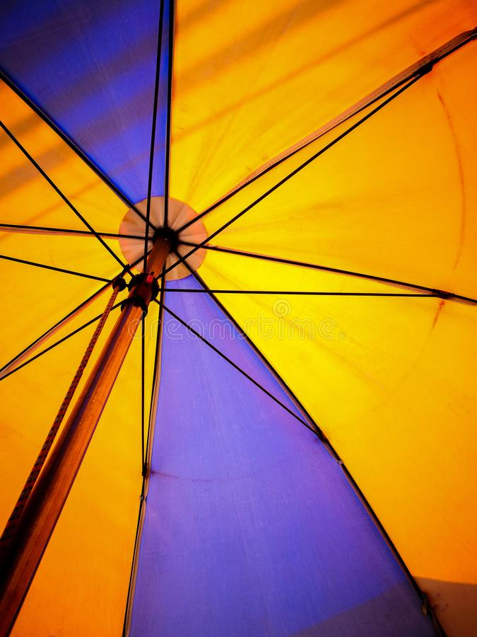 在背后照明的橙色和紫色沙滩伞 图库摄影