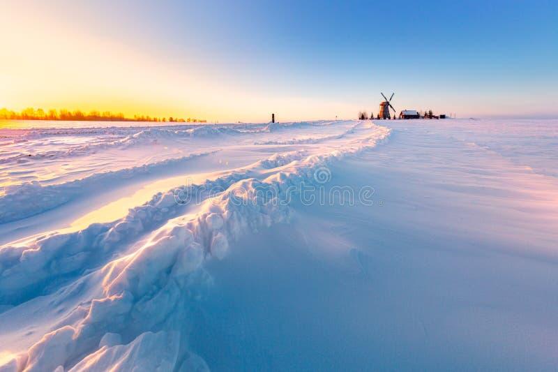 在背景冬天日出的木风车 Dudutki村庄,白俄罗斯 免版税库存照片