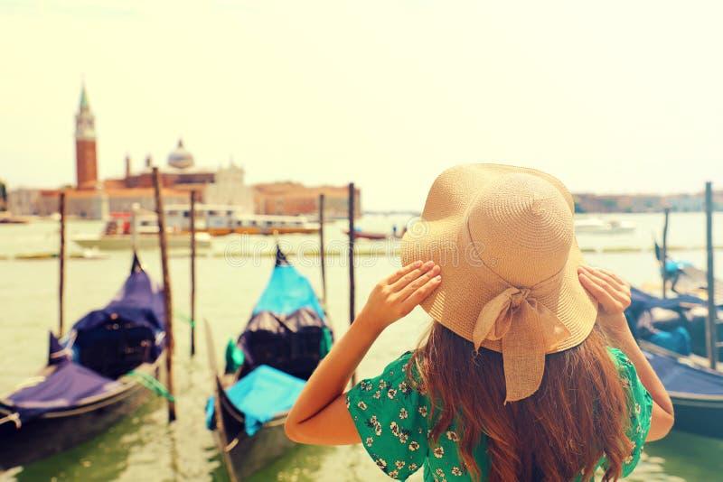 在背景的女孩拿着她的草帽用手的美丽的时尚在有风景的威尼斯和长平底船与火光点燃 免版税库存照片