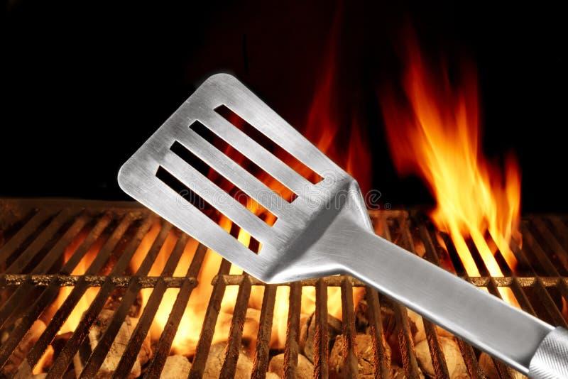 在背景的小铲接近的和烤肉火焰状格栅 库存照片