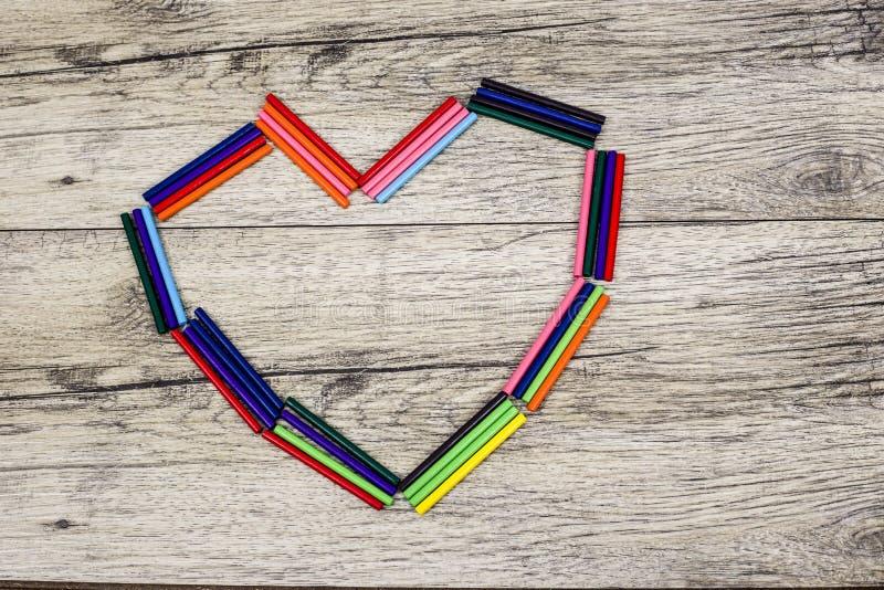 在背景的心形的五颜六色的木棍子 免版税库存照片
