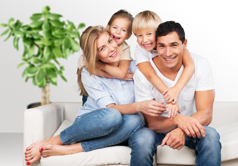 在背景的美丽的微笑的家庭 免版税库存图片
