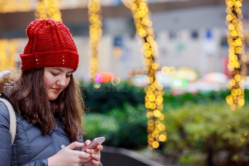 在背景的美好的少女藏品智能手机与bokeh光 图库摄影