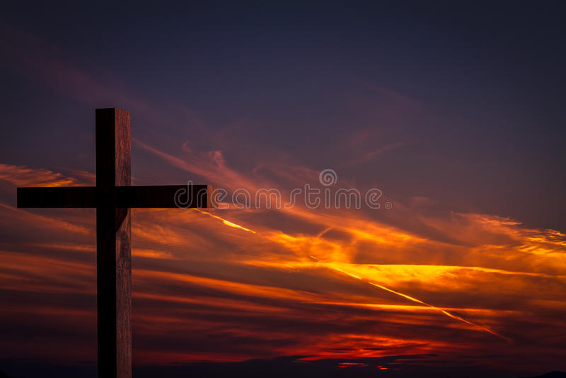 在背景的耶稣基督木十字架与剧烈,五颜六色的日落和桔子,紫色天空 免版税库存图片