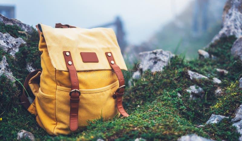 在背景绿草自然在山,被弄脏的全景风景,旅客的行家徒步旅行者旅游黄色背包放松 免版税库存照片