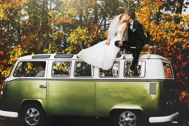 在背景美妙的秋天前面的快活的愉快的年轻夫妇 库存图片