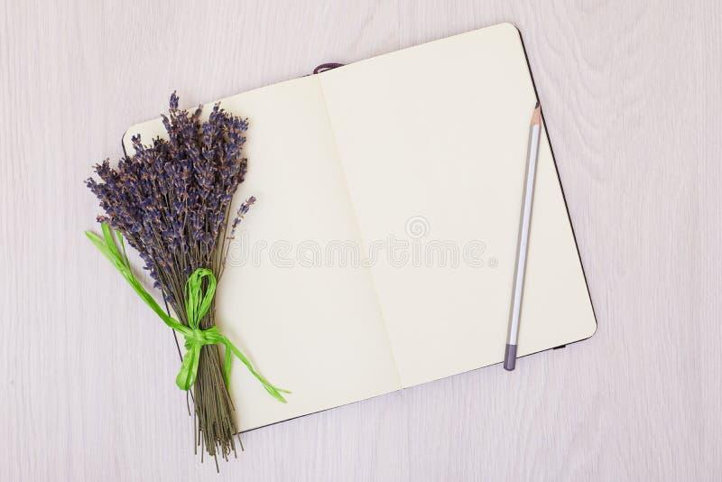 在背景顶视图嘲笑的淡紫色书桌 打开写生簿 笔记本 库存照片
