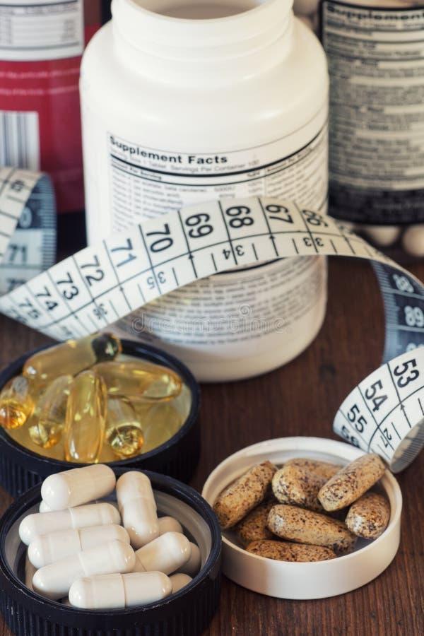 在胶囊和片剂的营养补充,在木背景 免版税库存照片