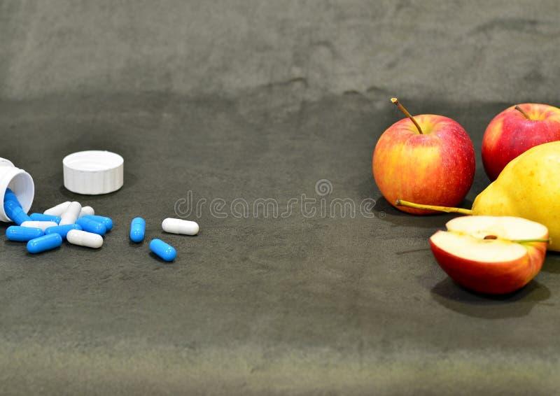 在胶囊和红色苹果的蓝色和白色维生素在桌上 免版税库存照片
