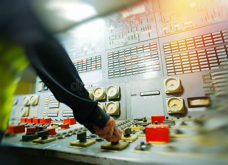 在能源厂的控制板的手 免版税库存图片