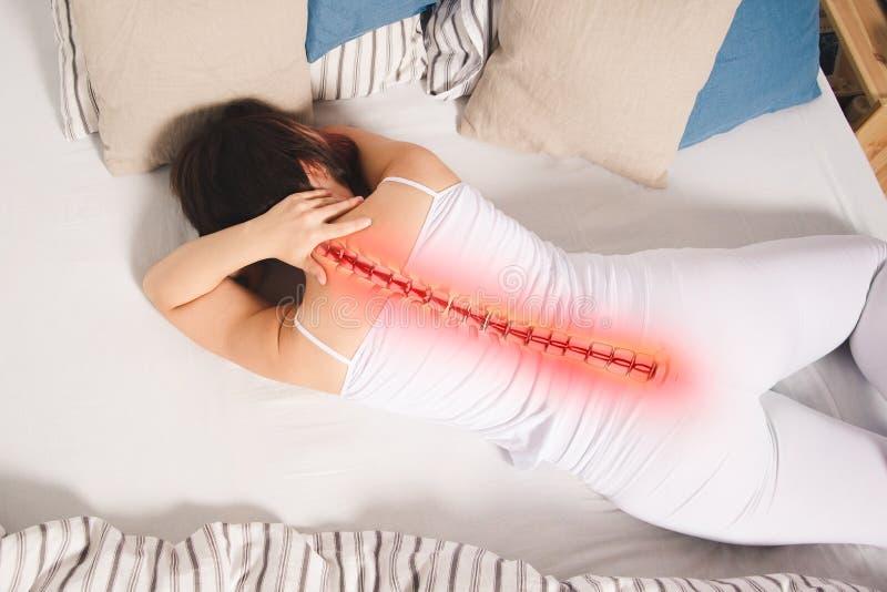 在脊椎的痛苦,妇女以在家腰疼,背部受伤 免版税库存图片