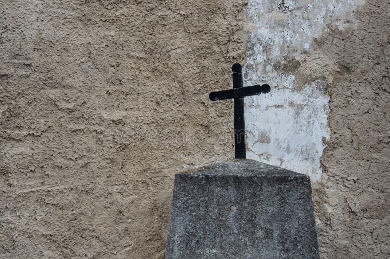 在脏的墙壁前面的黑金属十字架 免版税库存照片