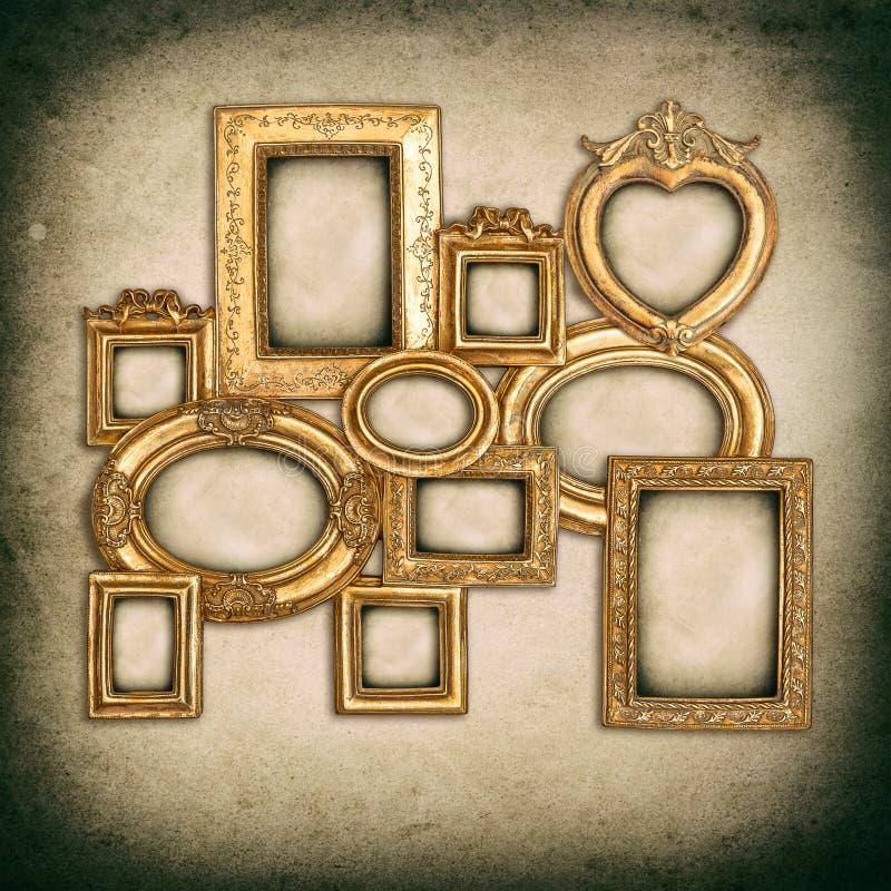 在脏的墙壁背景的古色古香的金黄框架 免版税库存图片