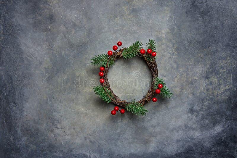 在脏的黑暗的石背景的传统手工制造圣诞节花圈绿色杉树分支枝杈霍莉莓果 顶视图 免版税库存图片