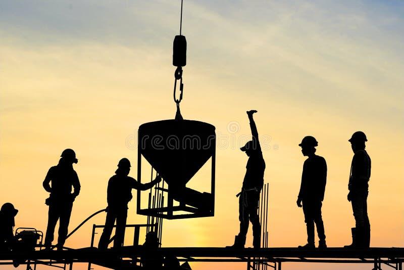 在脚手架框架模铸混凝土专栏的建筑工人立场剪影在美丽的太阳期间的建造场所 免版税库存照片