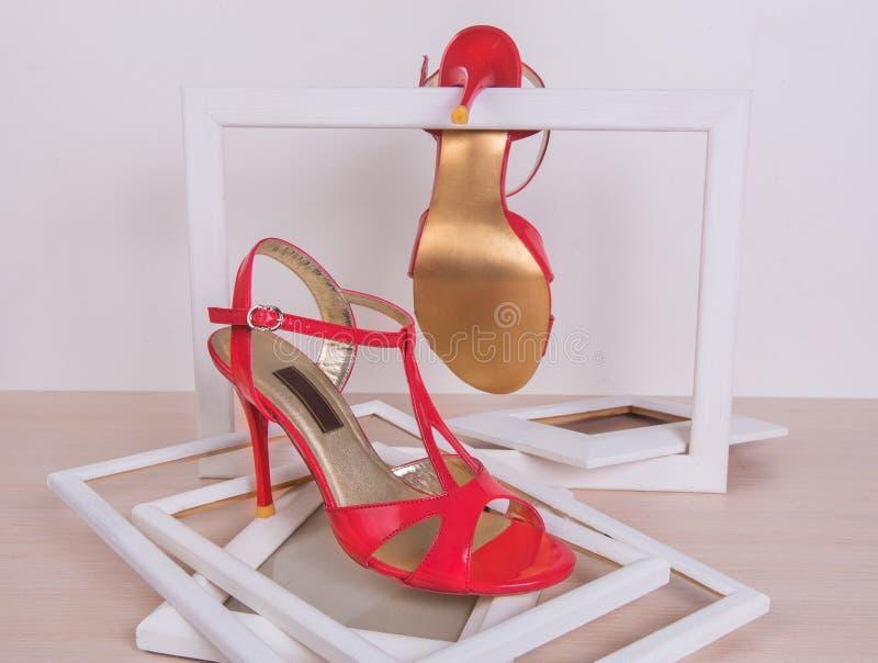 在脚跟的红色女性鞋子在一个白色背景框架 免版税图库摄影