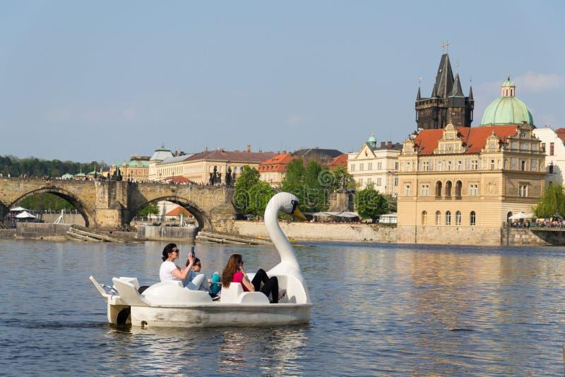 在脚蹬小船的旅游航行在查尔斯桥梁附近的伏尔塔瓦河河在布拉格,捷克 图库摄影