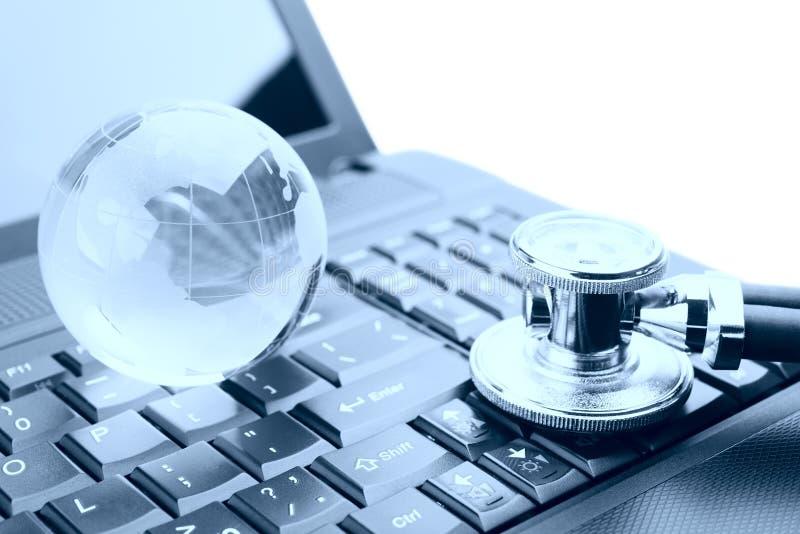 在膝上型计算机关键董事会的地球和听诊器 免版税库存照片