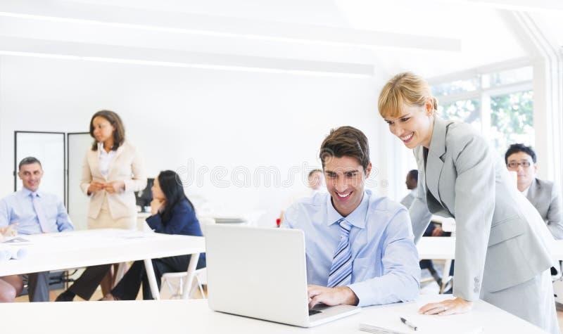 在膝上型计算机前面的一名上司引导的雇员 库存图片