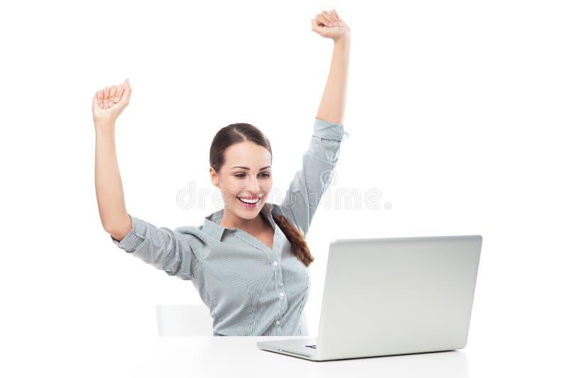 在膝上型计算机前面的妇女有被举的胳膊的