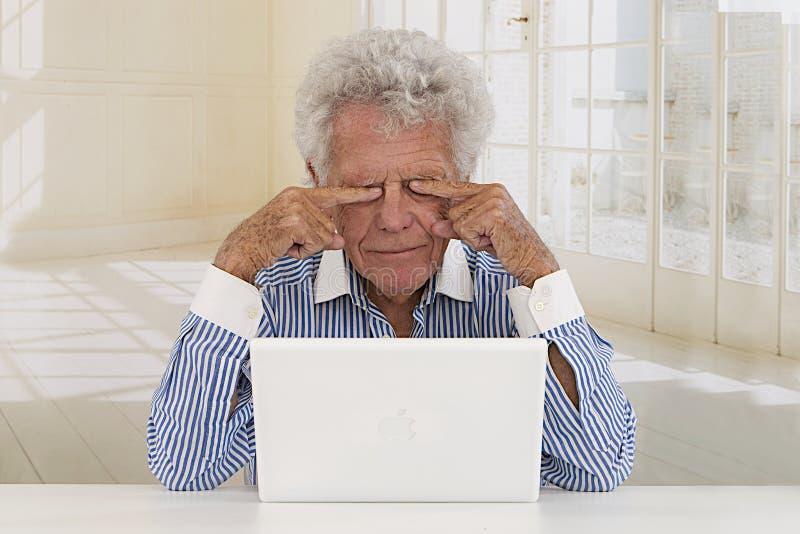 在膝上型计算机前面的疲乏的资深商人 库存照片