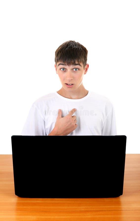 在膝上型计算机后的少年 图库摄影