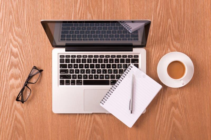 在膝上型计算机和咖啡杯的空白的笔记薄在木桌上 免版税库存图片