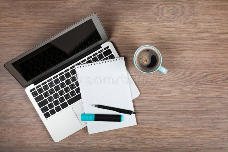 在膝上型计算机和咖啡杯的空白的笔记薄 免版税库存照片