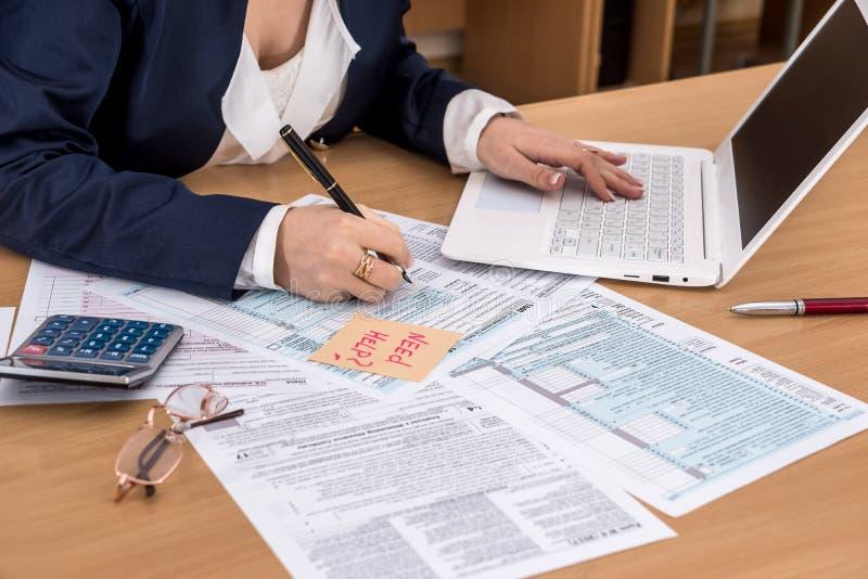 在膝上型计算机和填装的1040报税表的妇女工作 免版税库存图片