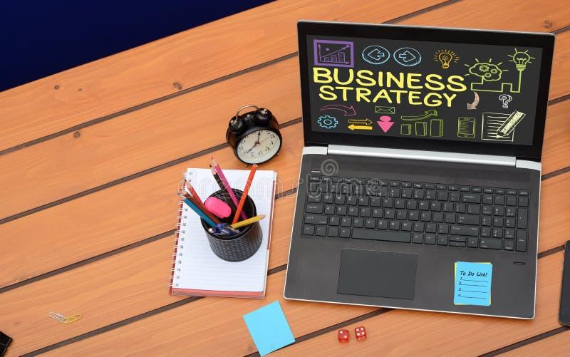 在膝上型计算机屏幕上的经营战略文本,在木背景的企业概念 图库摄影