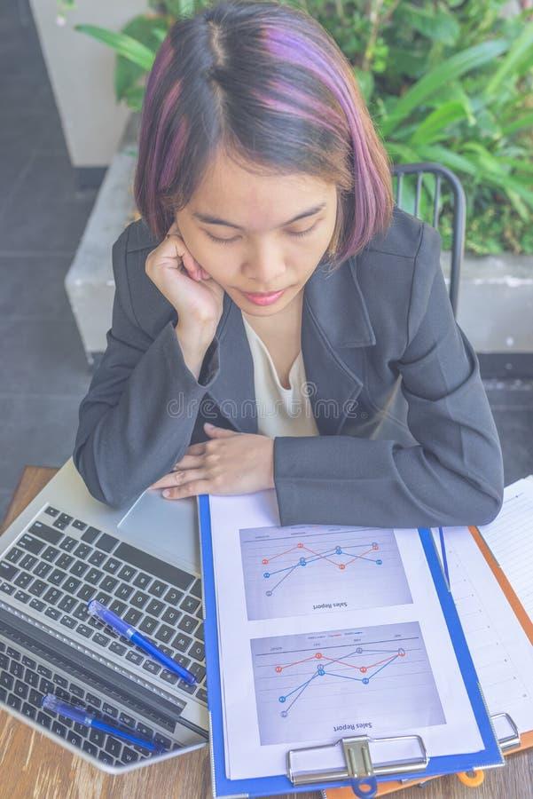 在膝上型计算机旁边的亚洲女实业家读书销售文件 免版税库存照片