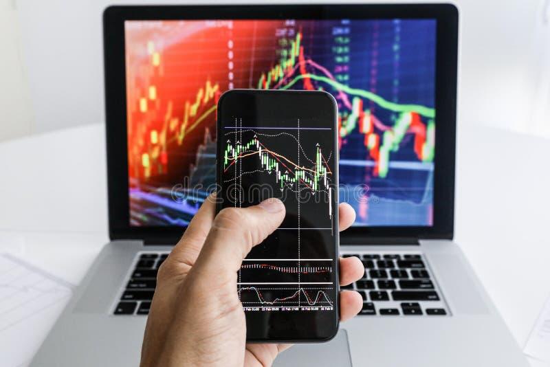 在膝上型计算机电话背景的商人  免版税库存照片