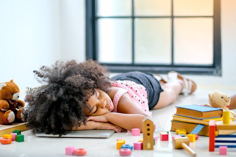 在膝上型计算机的一年轻非洲女孩睡眠在玩偶中,玩具和书和她在演奏比赛和玩具以后看轮胎 图库摄影