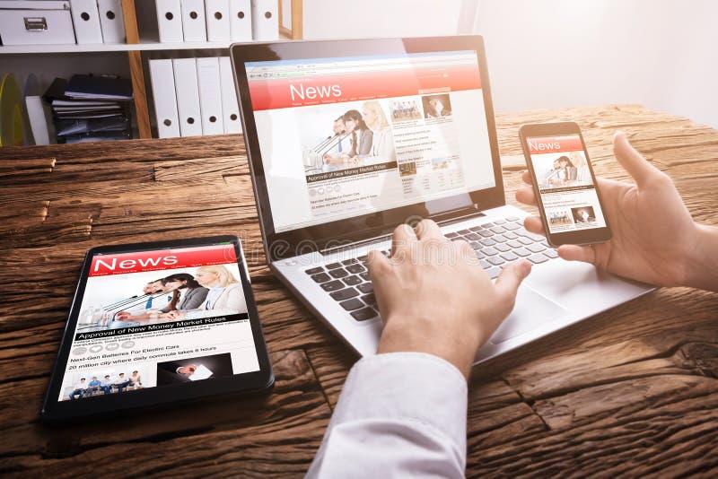 在膝上型计算机的买卖人读的网上新闻 库存图片
