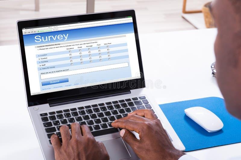 在膝上型计算机的人填装的调查形式 免版税库存照片