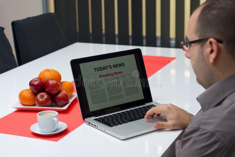 在膝上型计算机的人读书最新新闻 免版税库存照片