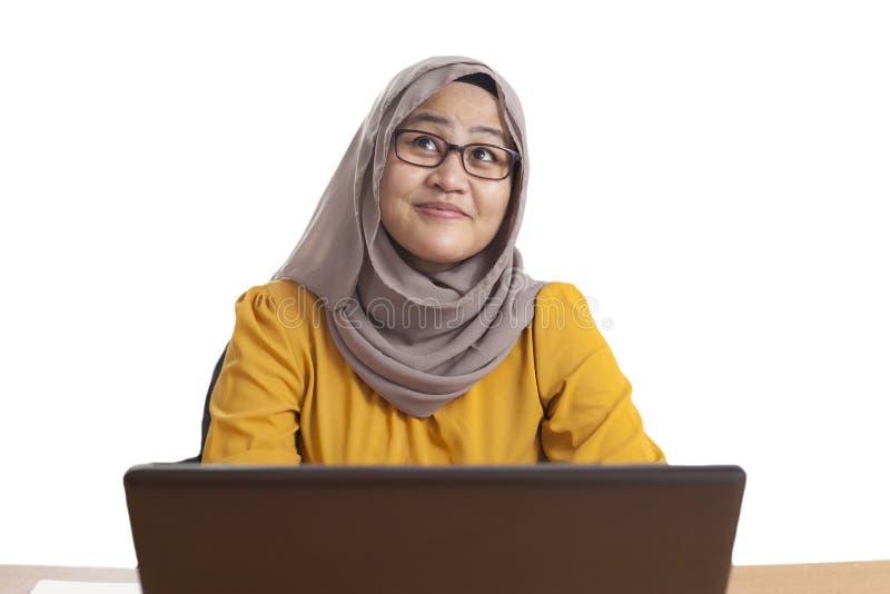 在膝上型计算机的回教女实业家工作在办公室,想法的姿态 免版税库存图片